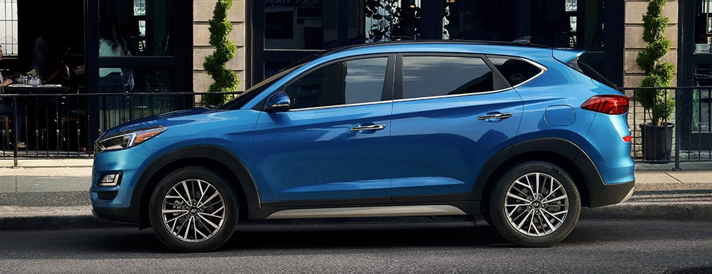 The side view of a blue 2020 Hyundai Tucson parked on the side of a city street.