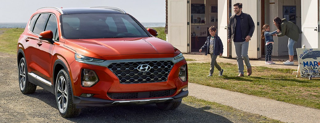The front view of a bright red 2020 Hyundai Santa Fe parked next to a family.