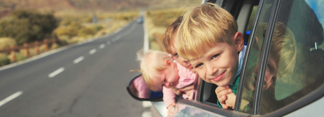 three kids hanging out the window of a car