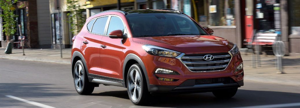 red 2018 Hyundai Tucson driving in a city
