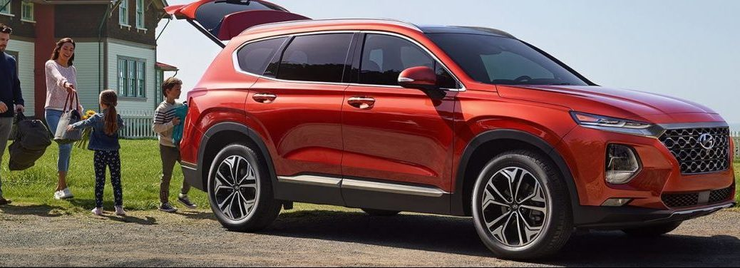 Family loads bags into the back of a red 2019 Hyundai Santa Fe.