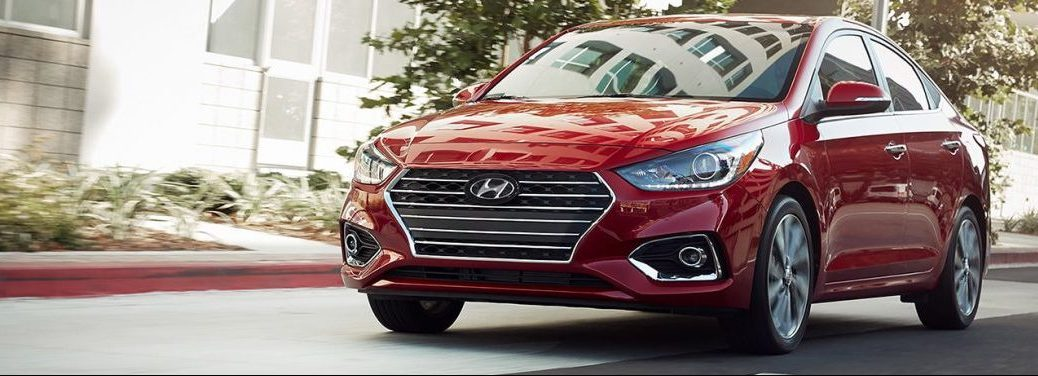 Red 2019 Hyundai Accent front-angled exterior view. Parked outside a house.