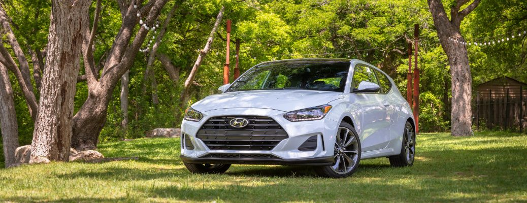 2019 Hyundai Veloster exterior shot with white paint color parked on grass under tree shade