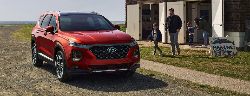 Two people walking towards red 2019 Hyundai Santa Fe