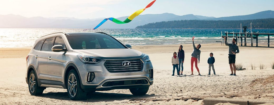 2019 Hyundai Santa Fe XL exterior shot with circuit silver paint color parked on a beach near the water as a family flies a rainbow kite