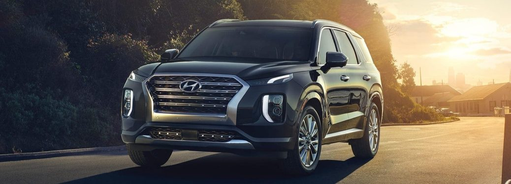 2020 Hyundai Palisade driving down road with trees in background from front drivers side view_o