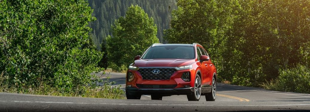 Red 2020 Hyundai Santa Fe driving down road from exterior front view