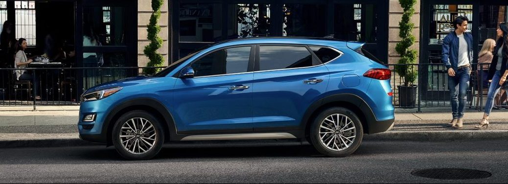 Blue 2020 Hyundai Tucson parked by a sidewalk in a city. Side view.