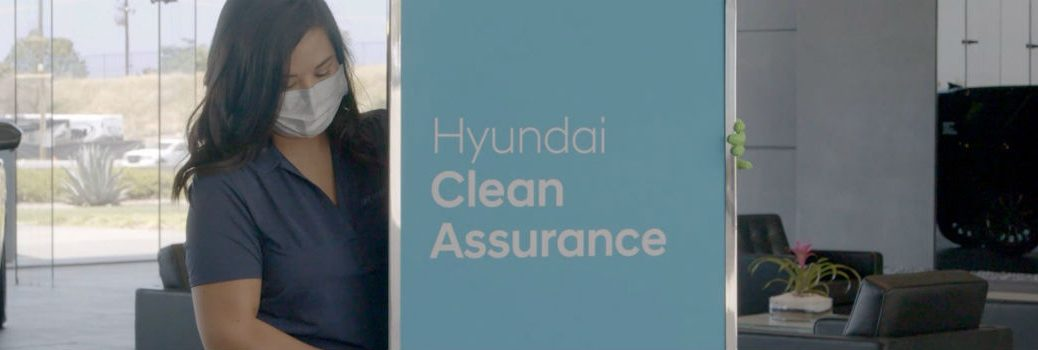Hyundai Clean Assurance Sign Being Wiped Down by Masked Employee