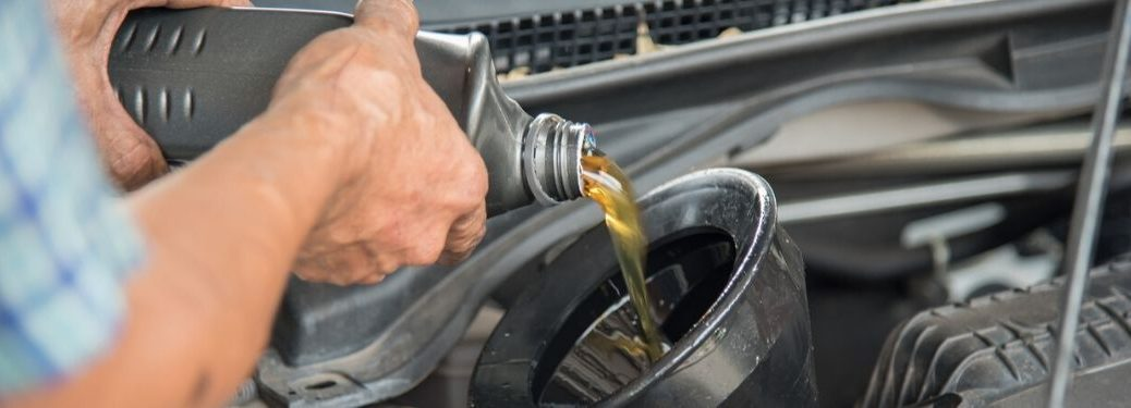 Mechanic pouring oil into engine