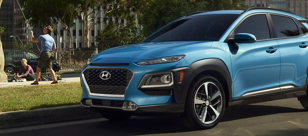 Blue 2021 Hyundai Kona parked in front of a garden