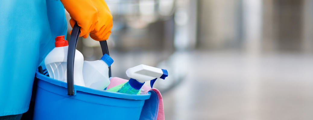 Closeup of hands wearing orange gloves and holding a bucket with cleaning supplies