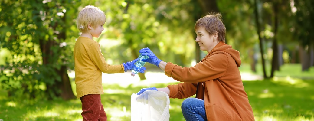 A woman and her young child picking up trash together in a park.