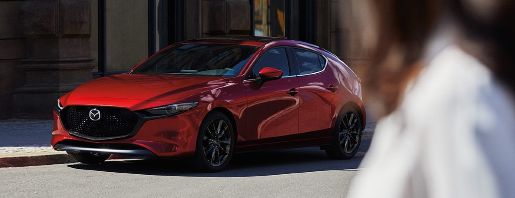 2020 Mazda3 hatchback red exterior front driver side parked on side of street blurry woman in right side