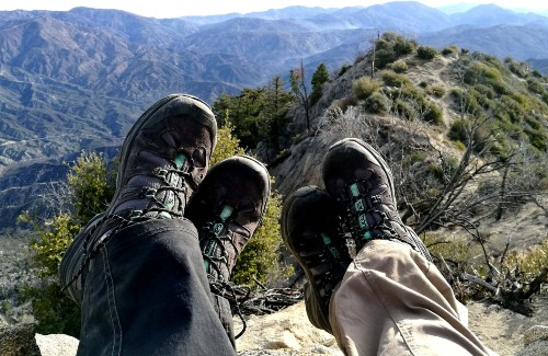 two pairs of feet with hiking shoes on mountain area