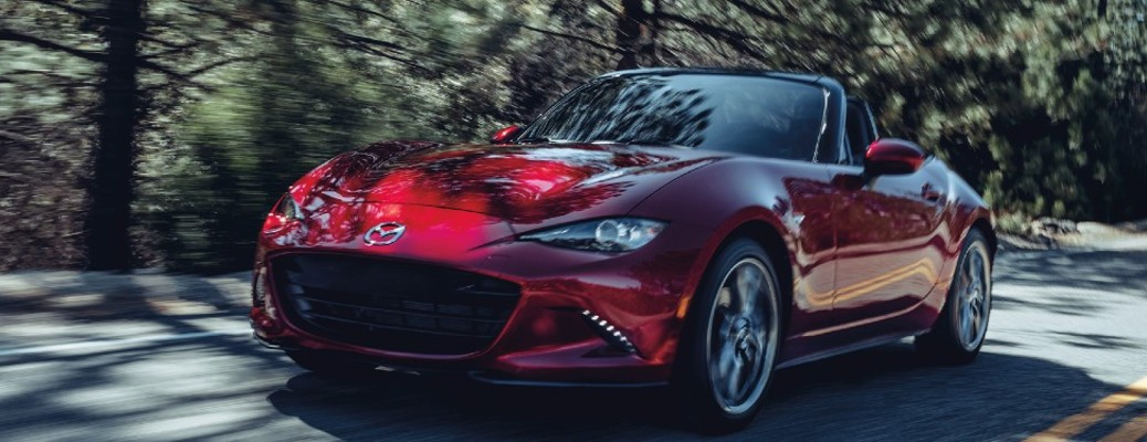2020 Mazda MX-5 Miata red exterior front driver side driving on road surrounded by trees