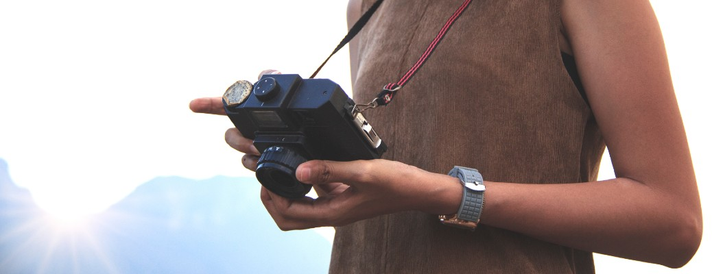 woman holding vintage camera in nature