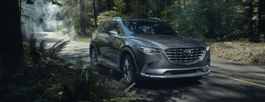 2021 Mazda CX-9 grey exterior front fascia passenger side driving on forest road