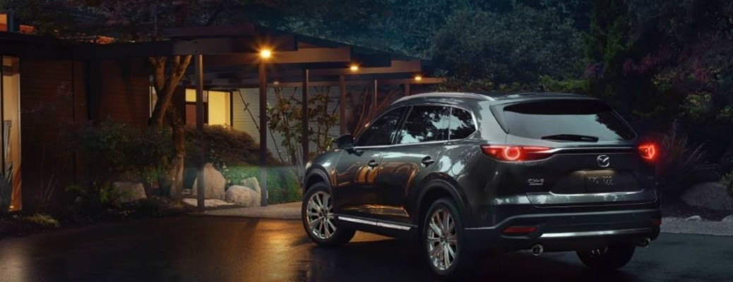 2021 Mazda CX-9 dark grey exterior rear fascia driver side parked in front of nice house