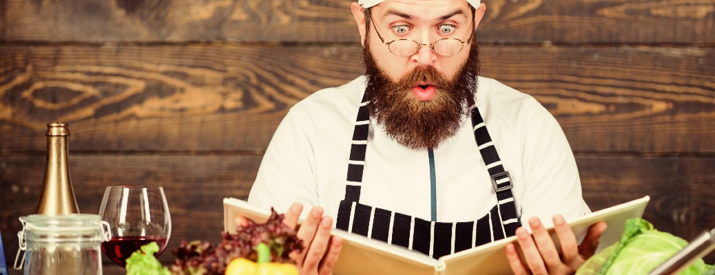 chef looking at recipe book with shocked expression