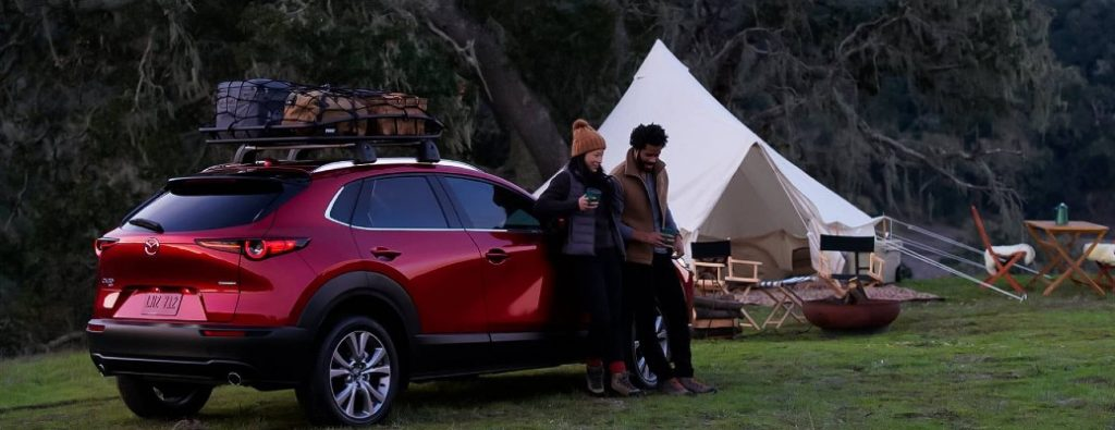 2021 Mazda CX-30 red exterior passenger side rear fascia couple camping in the woods