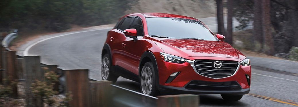 2021 Mazda CX-3 red exterior front fascia driving around curve on highway in the woods