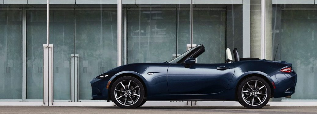 2021 Mazda MX-5 Miata blue exterior top down parked outside of building with glass doors
