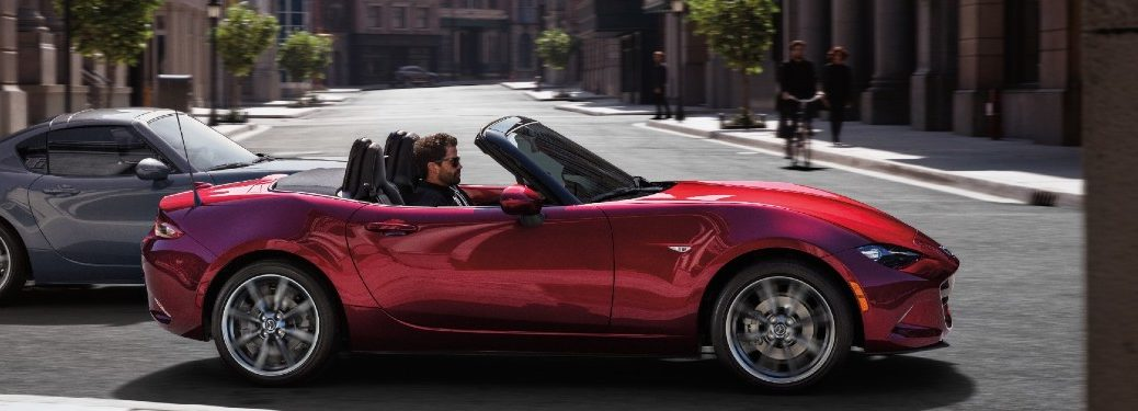 man driving 2021 Mazda MX-5 Miata with top down in city