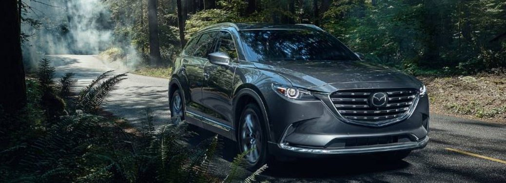 grey 2021 Mazda CX-9 front fascia passenger side driving on forest road