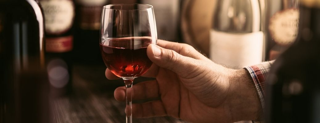 A man holds a glass of wine
