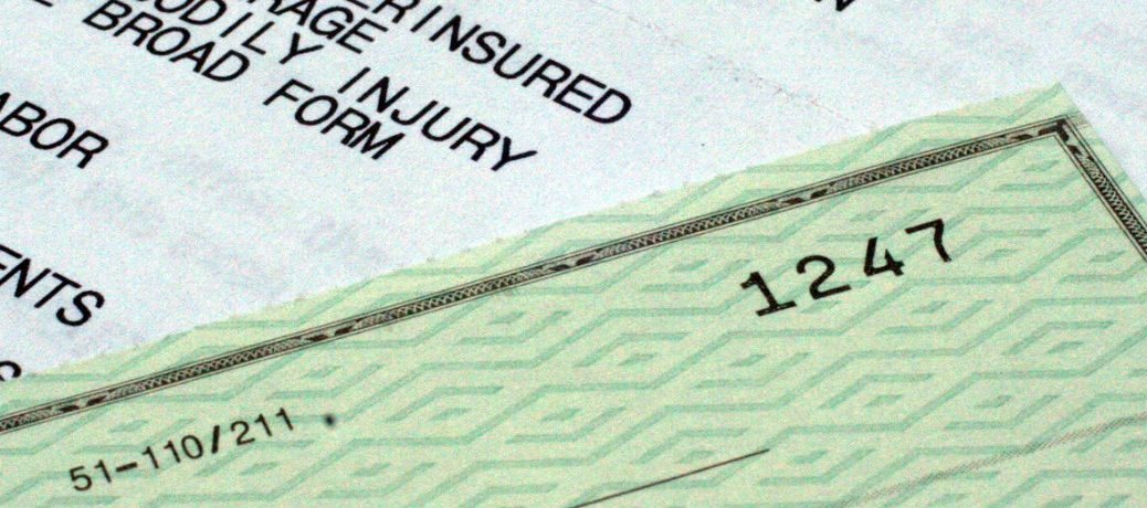 Close up of a check and insurance forms