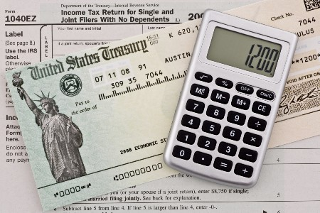 US Treasury stimulus check on a tax form with a calculator displaying 1200