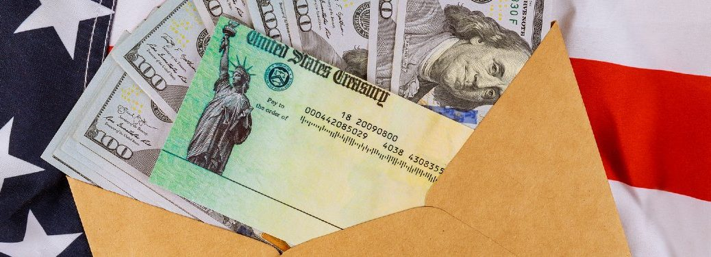 US Treasury stimulus check with one-hundred dollar bills on an American flag
