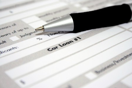 Pen on top of a car loan application form