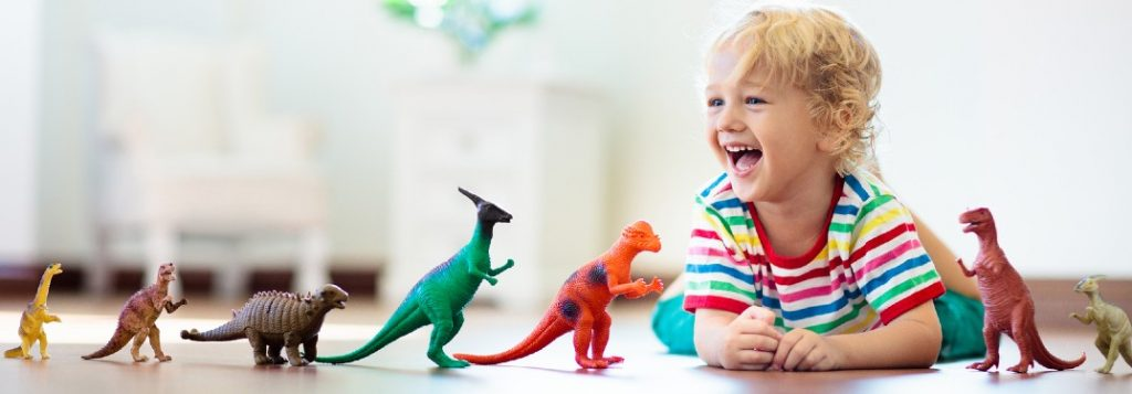Happy child with toy dinosaurs