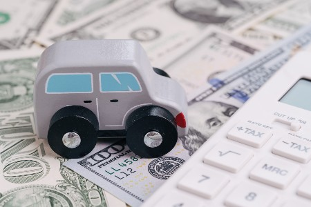 Toy car on top of money and next to a white calculator