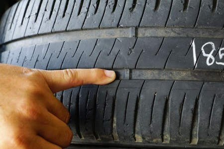 Person pointing at low tread on a car tire