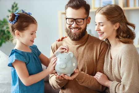 Happy couple holding a piggy bank with their daughter putting money inside of it