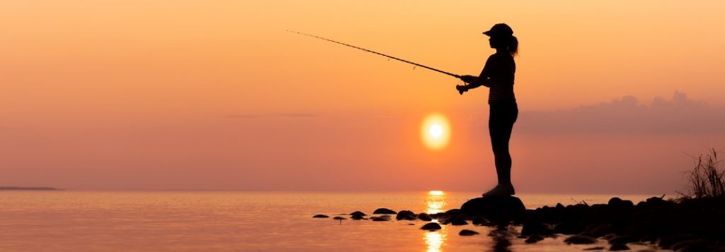 Woman fishing with a sunset in the background