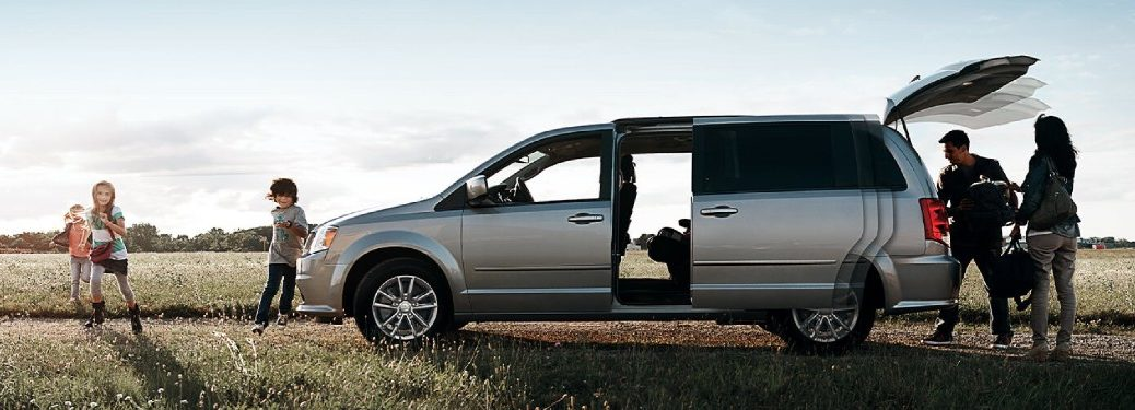 Driver angle of a silver 2020 Dodge Grand Caravan with its doors open and a family near it