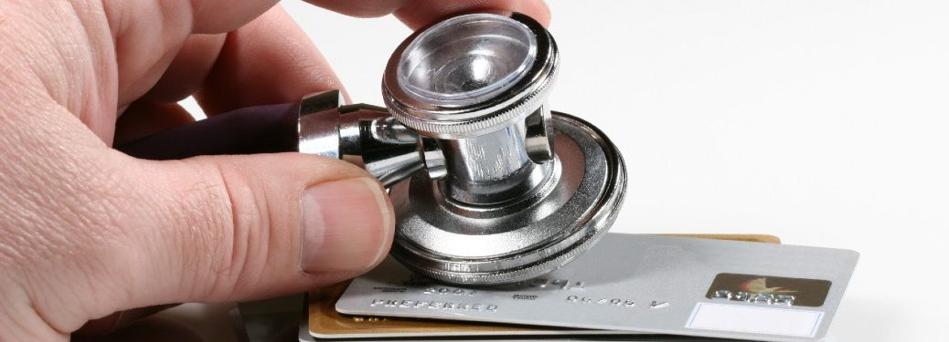 Person using a stethoscope on a pile of credit cards