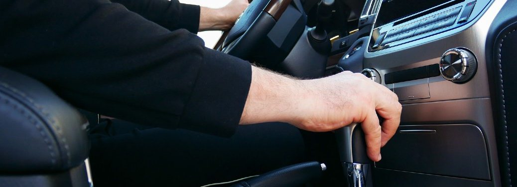 Driver with their hand on the gear shift inside a car
