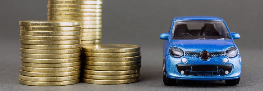 Stack of coins next to blue toy car