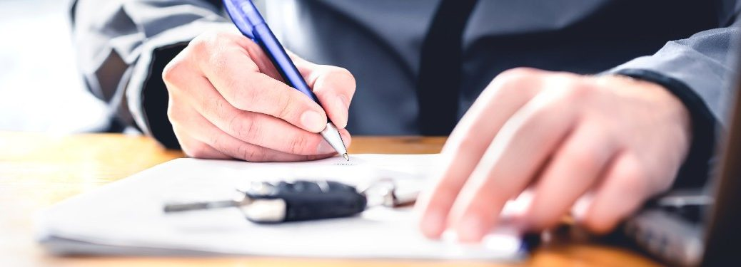 Person signing a car loan contract