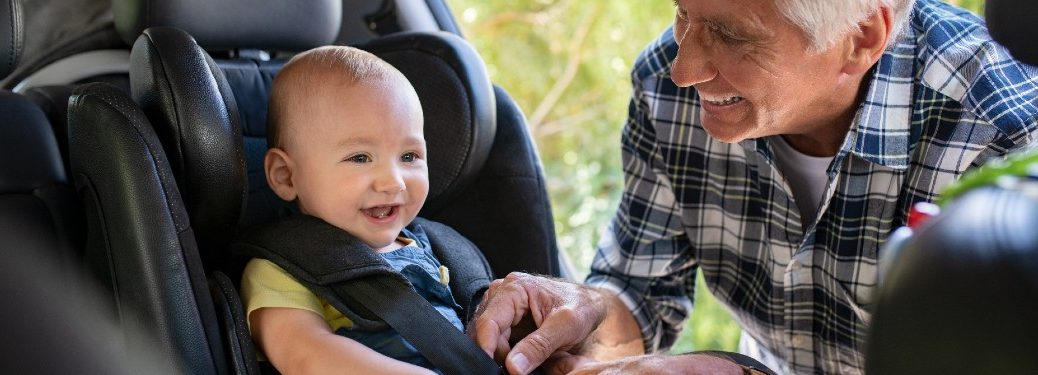 Grandfather buckling a baby boy into a car seat