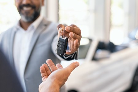 Happy salesman handing car keys over to another person
