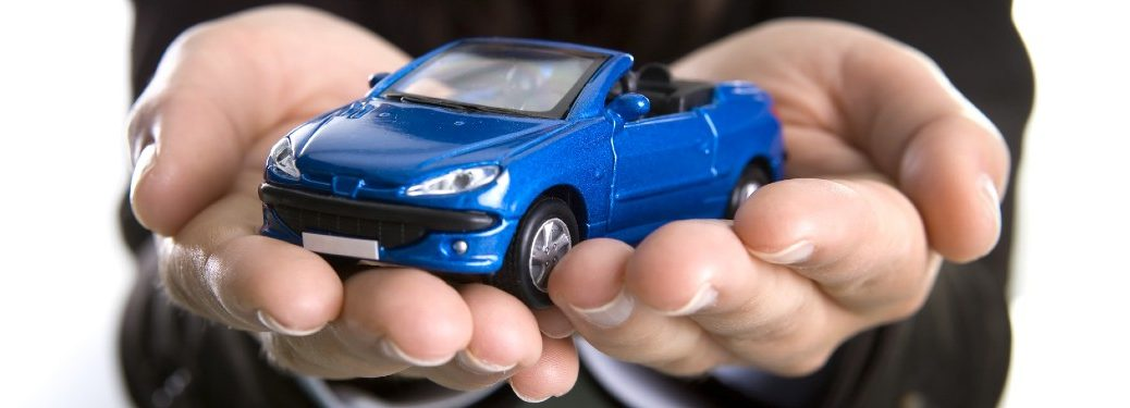 Business person holding a blue toy car in their hands