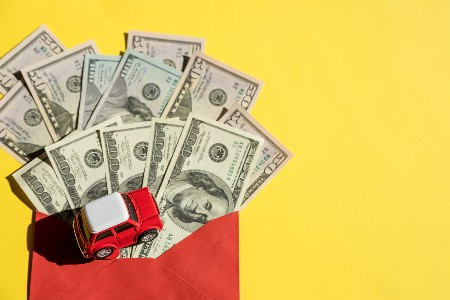 Toy car on top of money and a yellow background