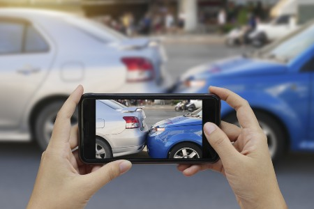 Person using a smartphone to take a picture of a car accident