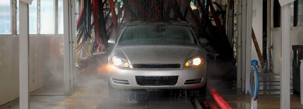 Front angle of a silver car going through a car wash